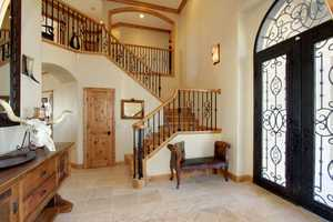 Just beyond the front entrance is a staircase complete with knotty alder finish work and hand-scraped hickory stairs.