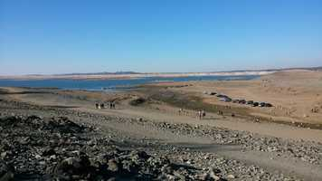During Jan. 2014, cars and people dotted Folsom Lake where water normally washed over the dry land.