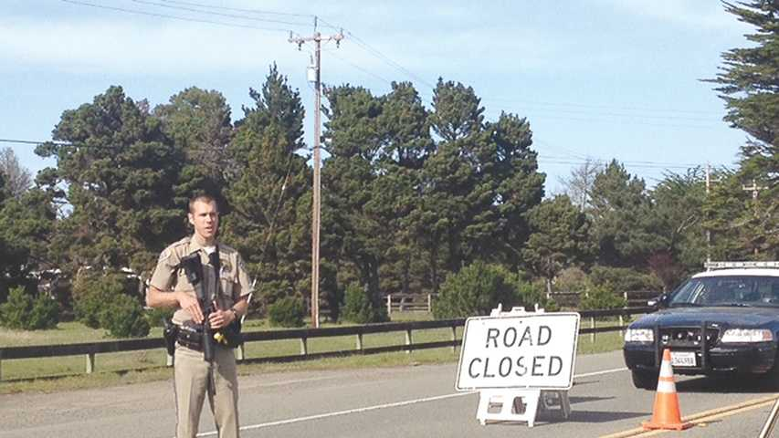 California Highway Patrol Officer John Hinke holds an AR-15 rifle while manning a roadblock on Highway 1 Wednesday afternoon (March 19, 2014).