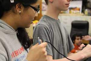 Senior Preethi Raju, who specializes in biology, helps set up for a mock-competition.