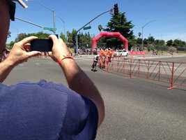A spectator takes photos of the riders during Stage 2 of the Amgen Tour of California in Folsom. (May 12, 2014)