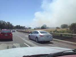 Firefighters are battling a grass fire in Sacramento near the American River Parkway that is causing problems for drivers along the Capital City Freeway because of the smoke.