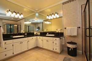 The bathroom has his and her walk-in closets, a jetted tub, double vanities and a shower stall with a glass block.