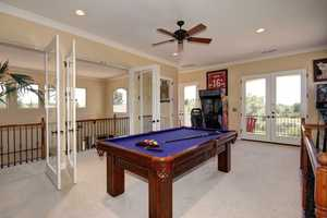 A pool table and arcade complete this loft/game room.