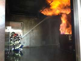 Isabelle Ford and Colin MacPherson practice battling a kitchen fire at the Roseville Fire Department's Kids Fire Camp.