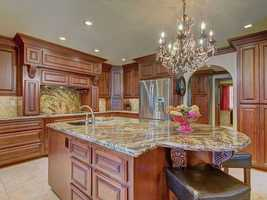 The kitchen features designer cabinetry, top-of-the-line appliances and stunning granite.