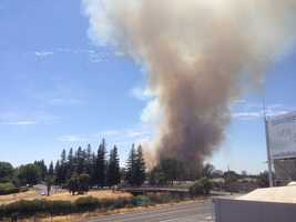A fire burning along the American River Parkway sent a large plume of smoke into the sky Saturday afternoon.