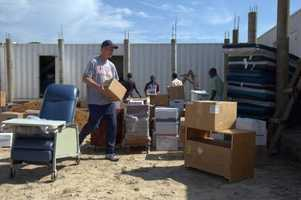 Dr. Chuck Tomek carrying out supplies donated by the Heartland