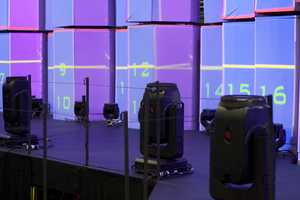 Lighting equipment seen in front of a hexagon wall projection screen.