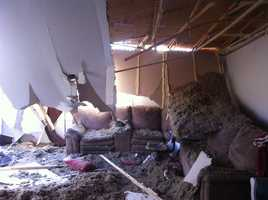 Here the roof collapsed on the Hobbs family's home dumping insulation and tornado debris in their living room.