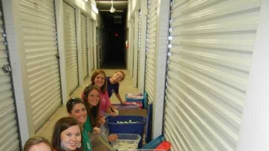 Members volunteering their time to organize the warehouse of donations for the League's That's My Bag effort.