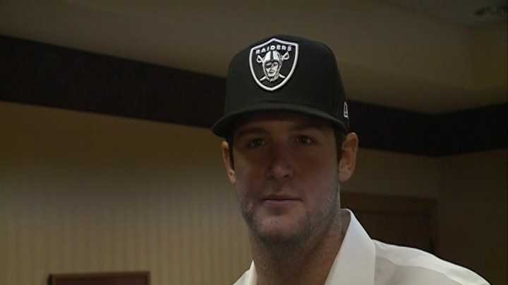 Tyler Wilson dons an Oakland Raiders hat after being selected in the fourth round of the NFL draft.