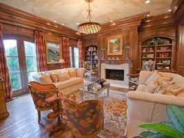 The parlor is ideal for receiving guests with beautifully wooded walls and natural light pouring through the full length windows.