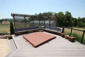 The deck extends further off of the house and turns into a hot tub area that can be enjoyed any season of the year.