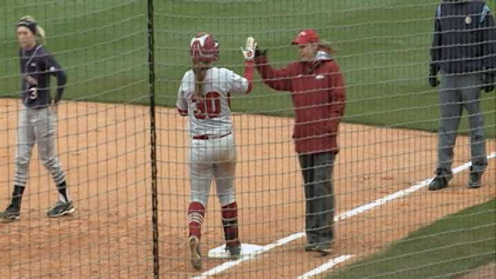 Devon Wallace is greeted by a Razorback assistant coach at first base after drawing a walk.