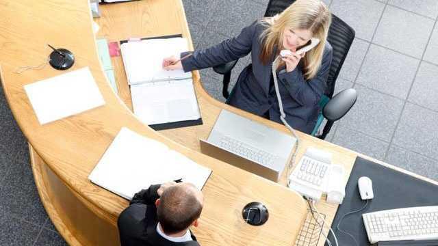 receptionist secretary sitting behind desk