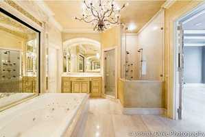 Look at this beautiful spacious bathroom that features a large tub, vanity, and shower that features several shower heads to surround the user in bathing bliss.