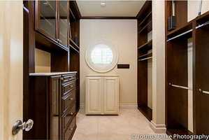 What a large walk in closet with beautiful dark wood inlays.