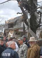 Officials with the Arkansas National Guard and the Arkansas Dept. of Emergency Management gather near a damaged home in tornado-ravaged Mena on April 10, 2009.