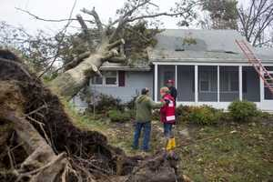 """The oak that shaded this home on Avon Court in Toms River, N.J., for 70 years yielded to Hurricane Sandy Monday, just half an hour after Bridget Dowd and Ken Mantila evacuated to her parents' home. Bridget's neighbors pitched in Tuesday afternoon to trim the fallen monster down to size and get a tarp over holes in the roof. """"Knock on wood, the water damage is not too bad,"""" Bridget told a Red Cross disaster volunteer."""