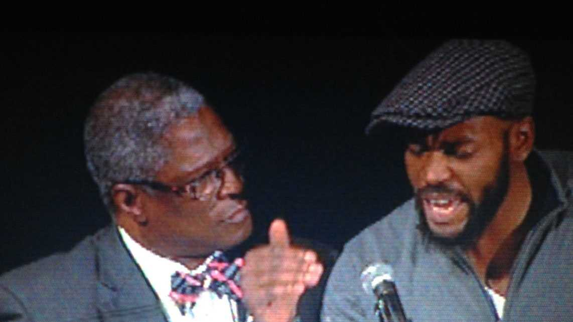Man on stage with Mayor Sly James