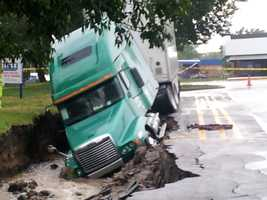 Viewer images of a tractor trailer that got stuck in a sinkhole that formed on Saturday afternoon after a big storm brought flooding rains to the metro.  The sinkhole was located in a parking lot in Mission, Kan.