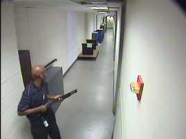 Alexis moves through the hallways of Building #197 carrying the Remington 870 shotgun. (FBI)