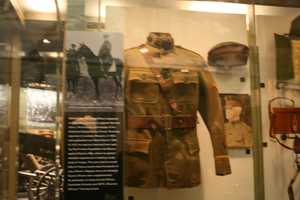Helmets and uniforms displayed in multiple gallery cases.