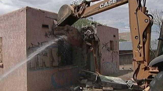 Crews smashed their ways through a crack house in northeast Albuquerque on Monday.