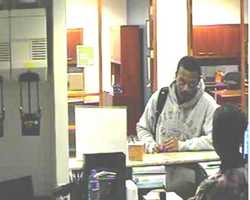 """This unknown suspect robbed a bank in Charlotte, North Carolina on May 1, 2013. He is described as a Black male with a mustache and wearing blue jeans and a gray hoodie with the word """"fitness"""" printed across the front. He carried a black and green backpack."""