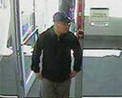 This unknown suspect robbed a bank in Pleasantville, New York on April 15, 2013. He wore a dark blue baseball cap with the letters 'NY' on the front of it, large-framed eye glasses, a blue hooded shirt, and gray pants that appeared to be sweatpants.