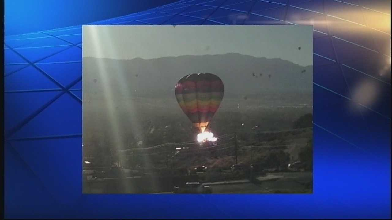 Two injured in balloon crash after their air balloon crashes into near by power lines and catches on fire.