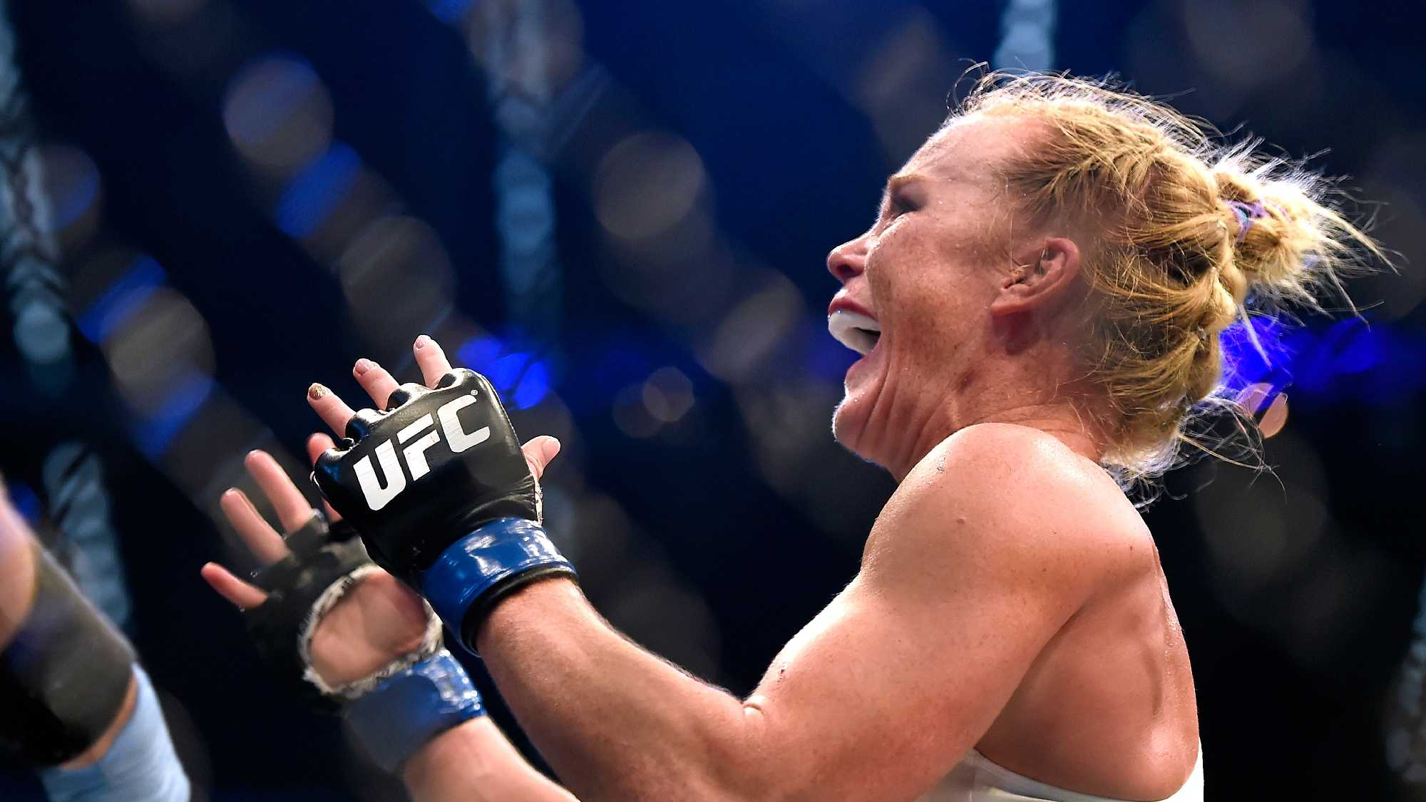 Holly Holm celebrates after defeating Ronda Rousey during their UFC 193 bantamweight title fight in Melbourne, Australia, Sunday, Nov. 15, 2015. (AP Photo/Andy Brownbill)