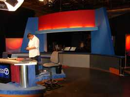 The Old Set Made NewHow did we do the news when we had no set?   Part of the old set was moved across the hall to our second studio, Studio A (our main studio is actually Studio B!)  It was no easy task moving the old set over and then re-lighting it. Here, production assistant Ruben Olguin puts the final touches on it.