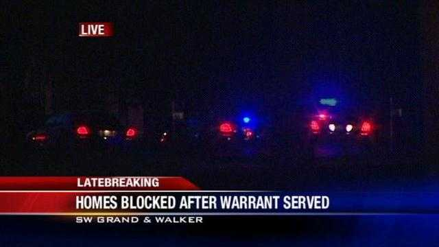 Oklahoma City police have closed a metro road following a warrant search that ended with several people in custody.