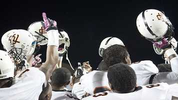 With arms and helmets held high, the Pirates celebrate a victory over the Jaguars.