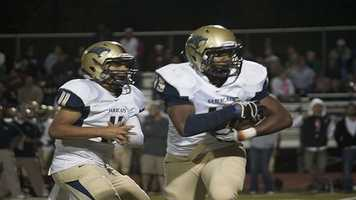 Southmoore's Tre Edwards (11) hands off to running back Karltrell Henderson (15).