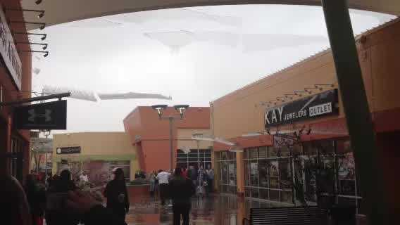 Ice sheets fall off the canopies at the Outlet Shoppes of Oklahoma