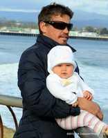 Darryl Virostko holds his daughter while watching waves on Santa Cruz' westside. / Photo by Erik Colasanti