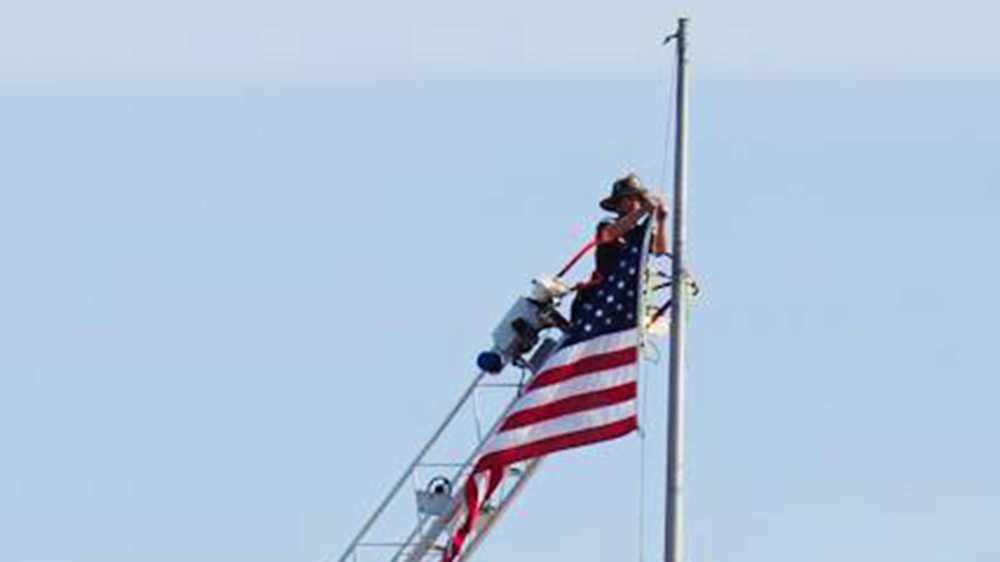A Santa Cruz firefighter lowers a flag on top of the clock tower on Pacific Avenue.