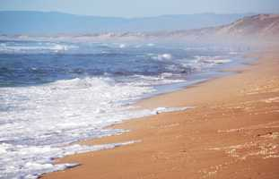 Offshore winds blew smoke over sanddunes at Fort Ord Dunes State Park out to the ocean Monday.
