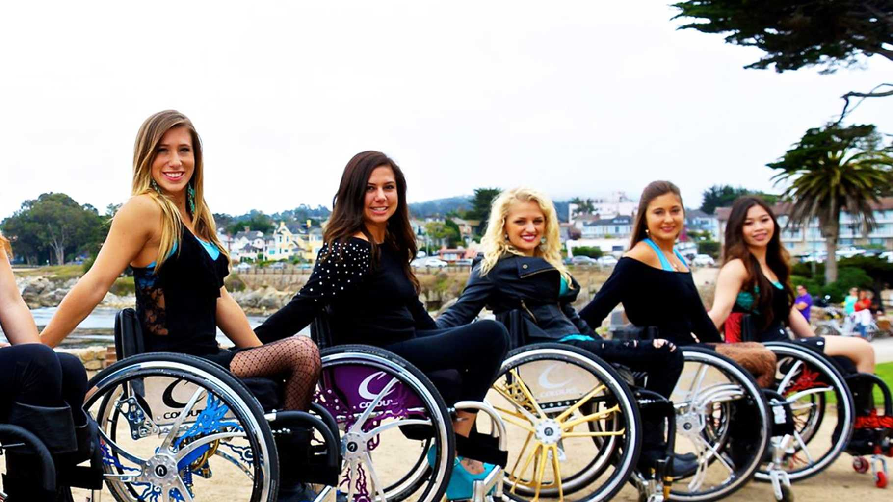 Chelsie Hill, left, smiles with her wheelchair dance team, Walk And Roll Dance Team.