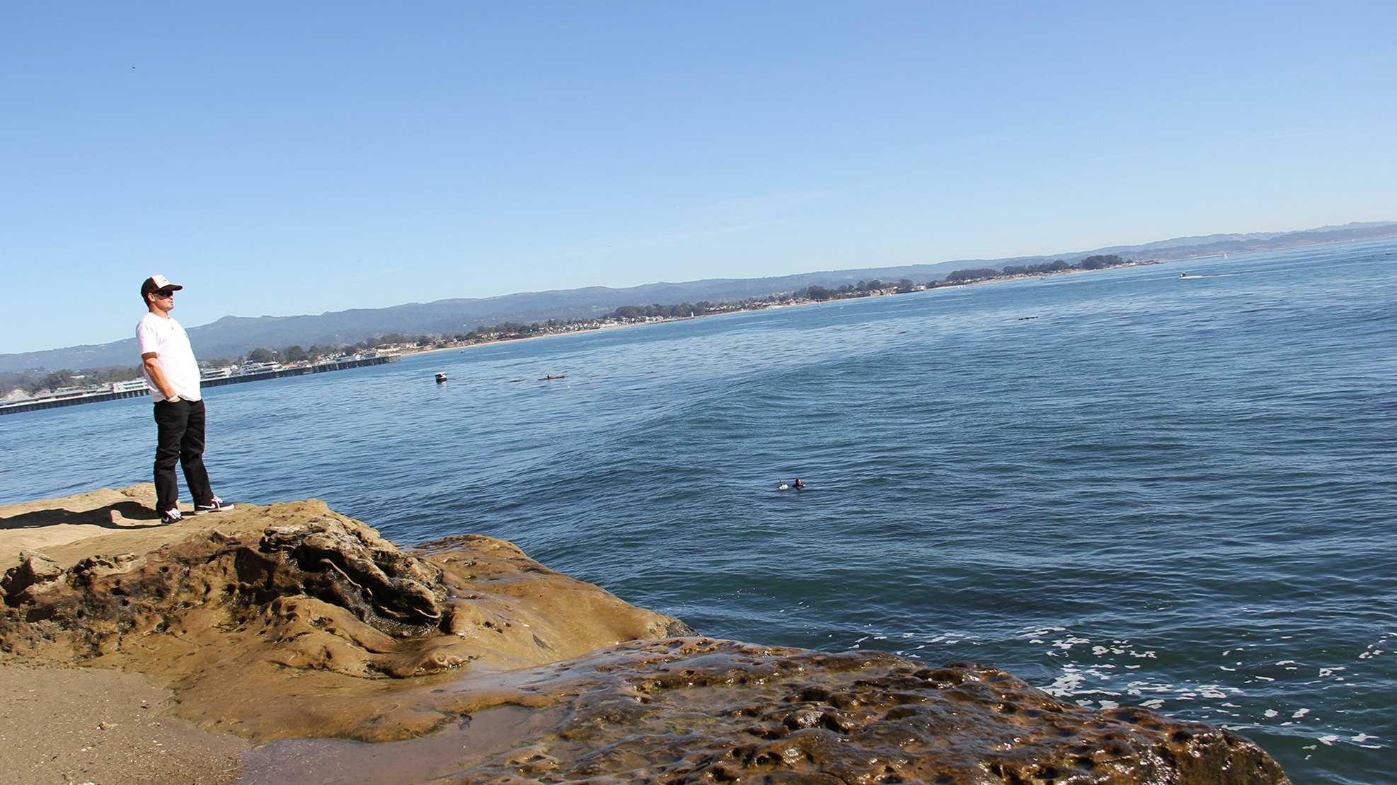 A Santa Cruz surfer watches the waves at Steamer Lane.