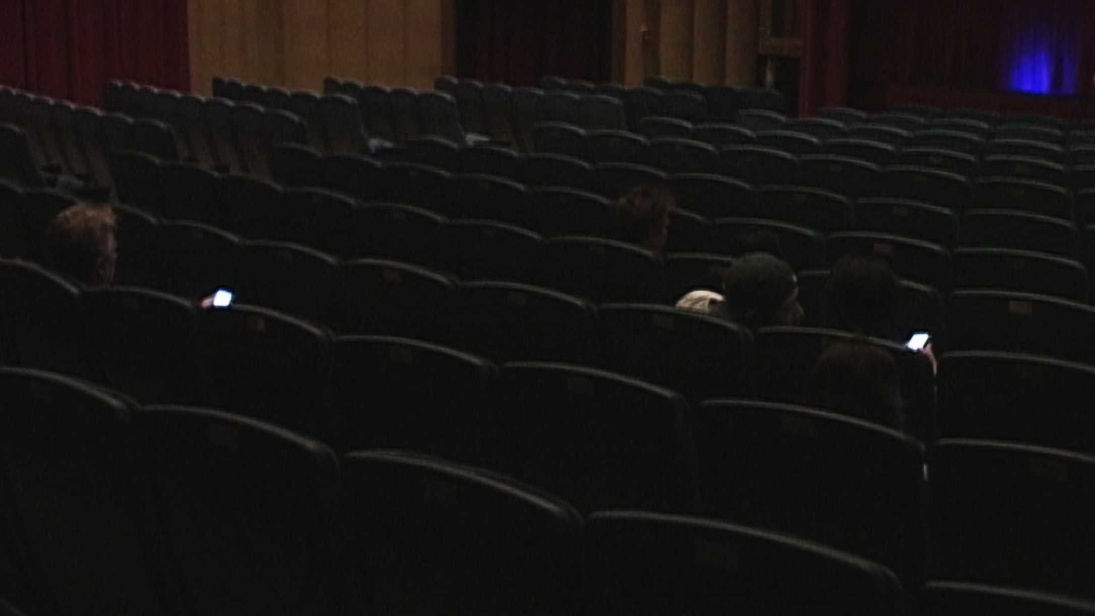 Smartphone screens light up inside the Nickelodeon Theater in Santa Cruz before a movie begins.