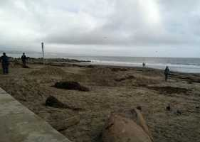Cleanup began Sunday after a high tide swept over beach walls in Capitola.
