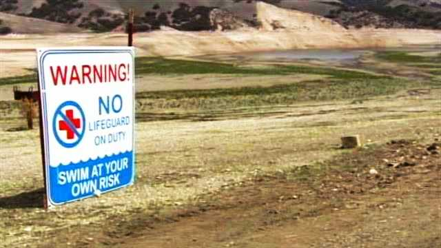 """A sign reading """"swim at your own risk"""" is seen at Lake San Antonio where water dried out."""