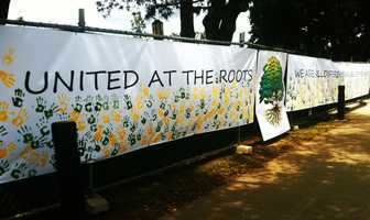 """Students created an enormous """"unity banner"""" to hang across their campus' entrance reading, """"United at the roots, we are all different branches of the same tree."""" Students dipped their hands in green and yellow paint buckets (the school's colors) and imprinted hundreds of hands across the banner."""