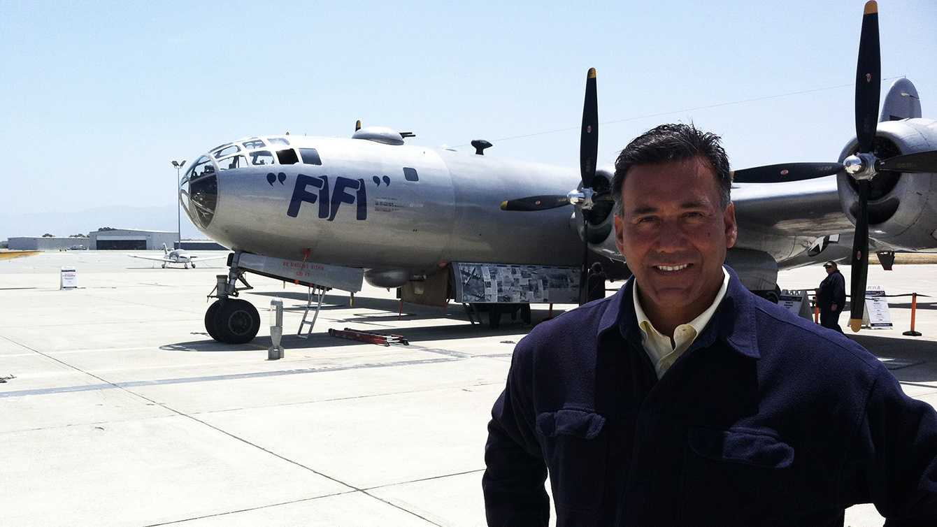 KSBW Reporter Felix Cortez stands next to FiFi the bomber plane in Salinas.