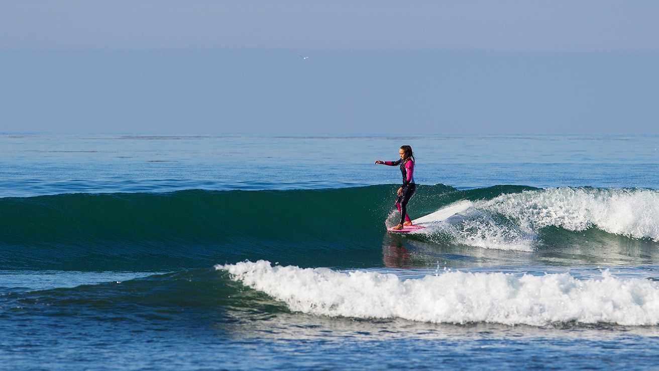 Meg Roh hangs five while riding her longboard on a fun glassy wave.