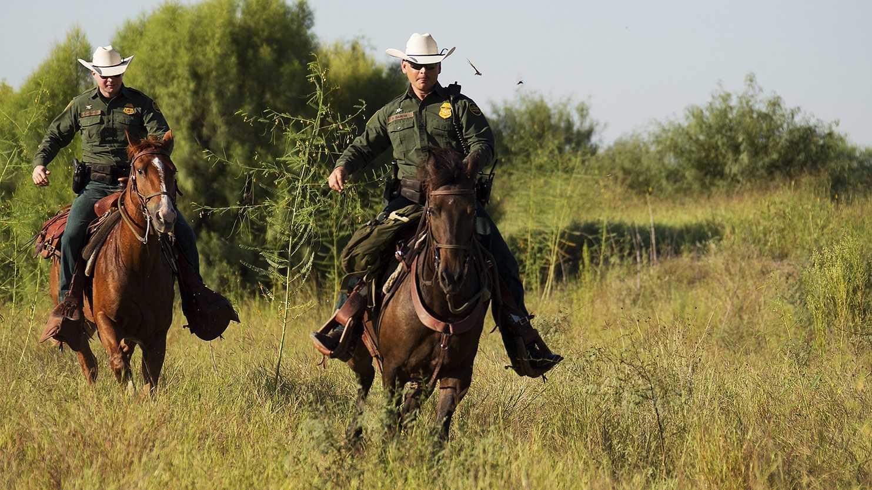 U.S. Border Patrol agents patrol the Mexico-US border on horseback in south Texas.